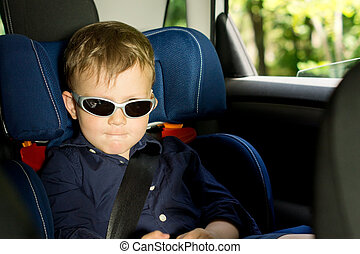 Young boy sitting in a child car-seat - Young boy biting the...