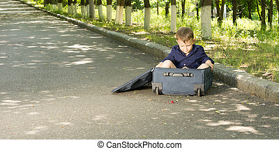 Little boy playing in a suitcase lying at the side of a...
