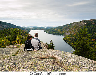 Couple sitting on top of a mountain