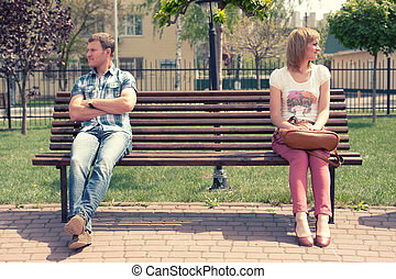 Young couple at quarrel on bench in park
