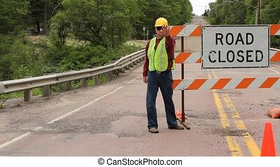 road closed sign - man directing traffic at a road closed...