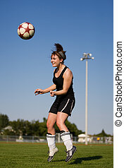 Soccer player - A female soccer player heading the soccer...