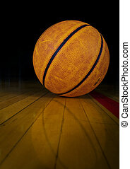 Basketball - A basketball on a dark gym floor with...