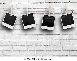 Photo frames with pins on rope over old aged brick wall