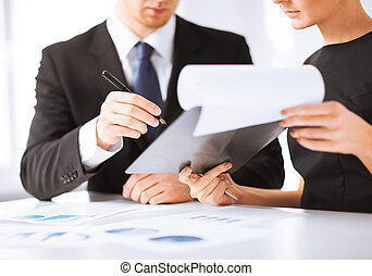 businessman and businesswoman signing paper - picture of...