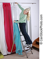 woman hanging up curtains