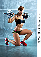 Young sports woman with barbell