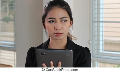 Asian Office Worker Using Tablet - An attractive female...