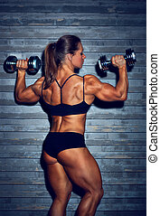 Woman bodybuilder with dumbbells backside view.