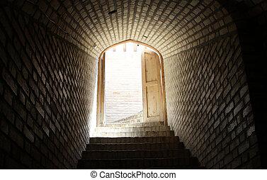 Open door and brick wall in corridor