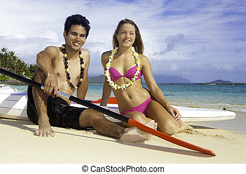 couple on the beach with paddleboards