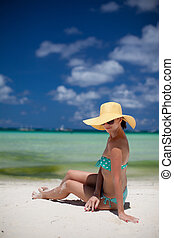 Woman sitting on beach in yellow hat - Woman sitting on...