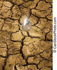 Water conservation - Water drop falling on parched, cracked...