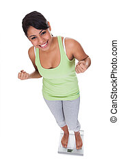 Happy Woman Standing On Weighing Scale Over White Background