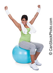Young Woman Sitting On Pilates Ball With Arm Raised Over...