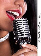 joven, mujer, canto, en, micrófono