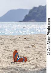 flip-flop on the beach. - Orange flip-flop on the beach