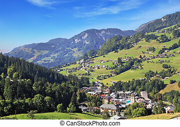 The small village - Swiss Alps. Alpine meadows on gentle...