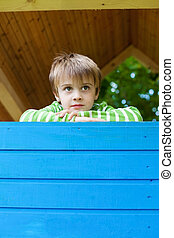 Young cheerful boy inside a blue playhouse - Young cheerful...