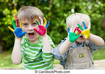 two children showing painted hands outside - Two children...