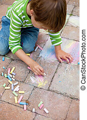 boy playing with chalk on pavement - Little boy drawing with...