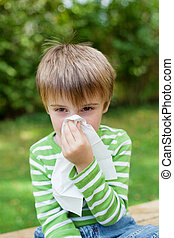 Boy with allergy covering his nose - Little boy covering his...