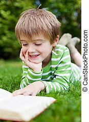 Happy little boy reading book in the garden - Happy little...