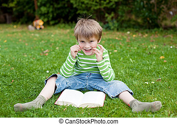 Cheerful little boy reading book on the grass - Cheerful...