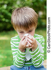 Little boy blowing his nose in the garden - Little boy...