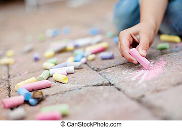 Colorful chalk on the pavement - Little boy hands painting...