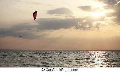Kite surfer sailing on the sea at sunset