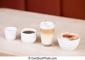 Coffees Displayed In A Row On Wooden Table