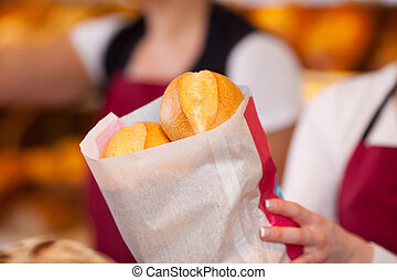 Bakery Worker Holding Bag Of Breads - Closeup of female...