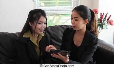 Asian Office Workers Discuss Work - Two attractive female...