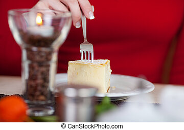 woman eating cheese cake in a café