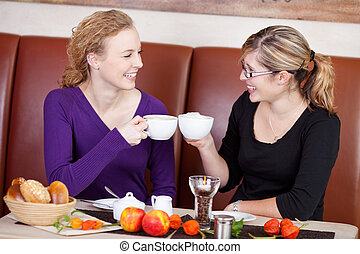 Friends Toasting Coffee Cups At Cafe Table - Happy female...