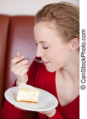 beautiful woman enjoying cheese cake - blond woman enjoying...