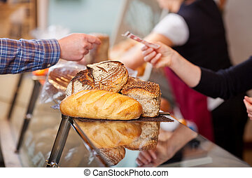 Customer Paying For Breads At Bakery Counter - Closeup of...
