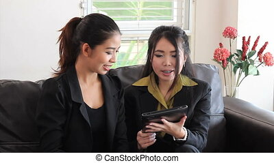 Asian Office Workers Using Tablet - Two attractive female...