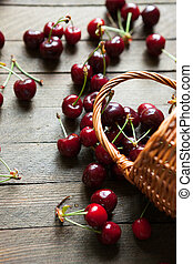 Ripe cherries in bulk on a table and a basket, food