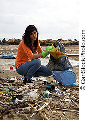 Young social worker cleaning dirty beach - Environmental...