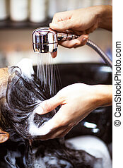 Hair Washing - Brown-haired woman having her hair washed at...