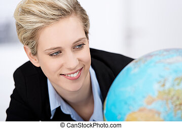 Businesswoman Looking At Globe In Office - Closeup of young...