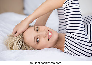 Happy Young Woman Lying On Bed - Closeup portrait of happy...