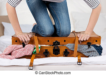 Young Woman Packing Suitcase On Bed - Midsection of young...