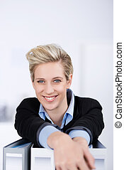 Smiling Businesswoman With Ring Binders At Desk