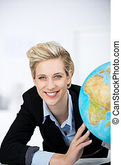 Smiling Businesswoman With Globe In Office - Closeup of...