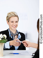 Businesswoman Receiving Cardkey From Receptionist - Happy...