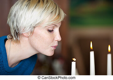 Woman Blowing Candle In Restaurant - Closeup of young woman...