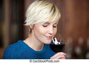 Blond Woman Drinking Red Wine In Restaurant - closeup...